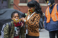 FILE - In this Monday, March 29, 2021, file photo, Jenea Edwards, of the North Side, helps her son Elijah, 9, in the third grade, with his mask before heading into Manchester Academic Charter School on the first day of in-person learning via a hybrid schedule, in Pittsburgh. Dozens of school districts around the country have eliminated requirements for students to wear masks, and many more are likely to ditch mask requirements before the next academic year. (Andrew Rush/Pittsburgh Post-Gazette via AP, File)