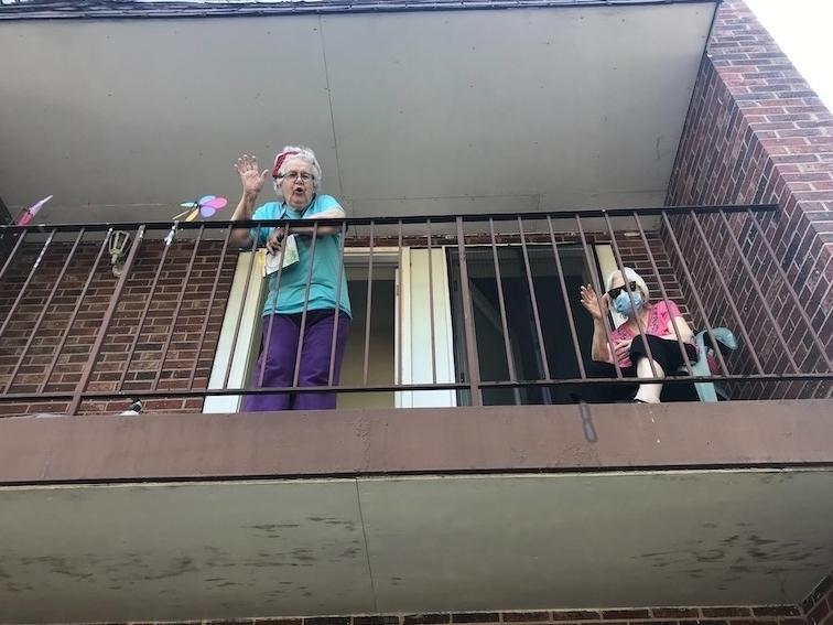 Unable to leave their suites, Moraine Court residents in lockdown from COVID-19 wave from their balconies.