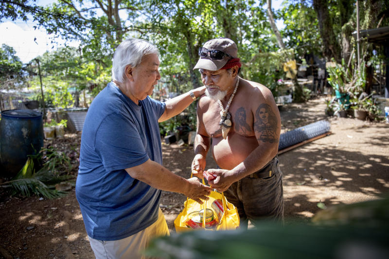 """Leo Tudela, left, brings food for Everett Torregrosa as he visits his home in Hagatna, Guam, Thursday, May 9, 2019. """"We're like brothers,"""" said Torregrosa of Tudela who checks on him periodically after learning they each were victims of sexual abuse by priests when they were boys. (AP Photo/David Goldman)"""
