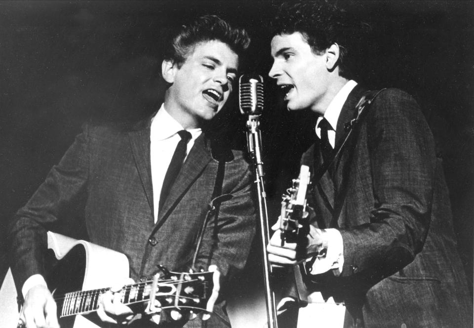 FILE - In this July 31, 1964 file photo The Everly Brothers, Phil, left, and Don, perform on stage. Don Everly, one-half of the pioneering rock 'n' roll Everly Brothers whose harmonizing country rock hits impacted a generation of rock music, has died. Don Everly was 84. A family spokesperson said Everly died at his home in Nashville, Tennessee on Saturday, Aug. 21, 2021. (AP Photo, File)