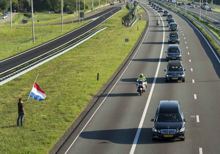 A man holds a Netherlands flag flying at half-mast (L) as a row of hearses carrying victims of the Malaysia Airlines flight MH17 plane disaster are escorted on highway A27 near Nieuwegein by military police, on their way to be identified by forensic experts in Hilversum, July 23, 2014. REUTERS/Marco de Swart