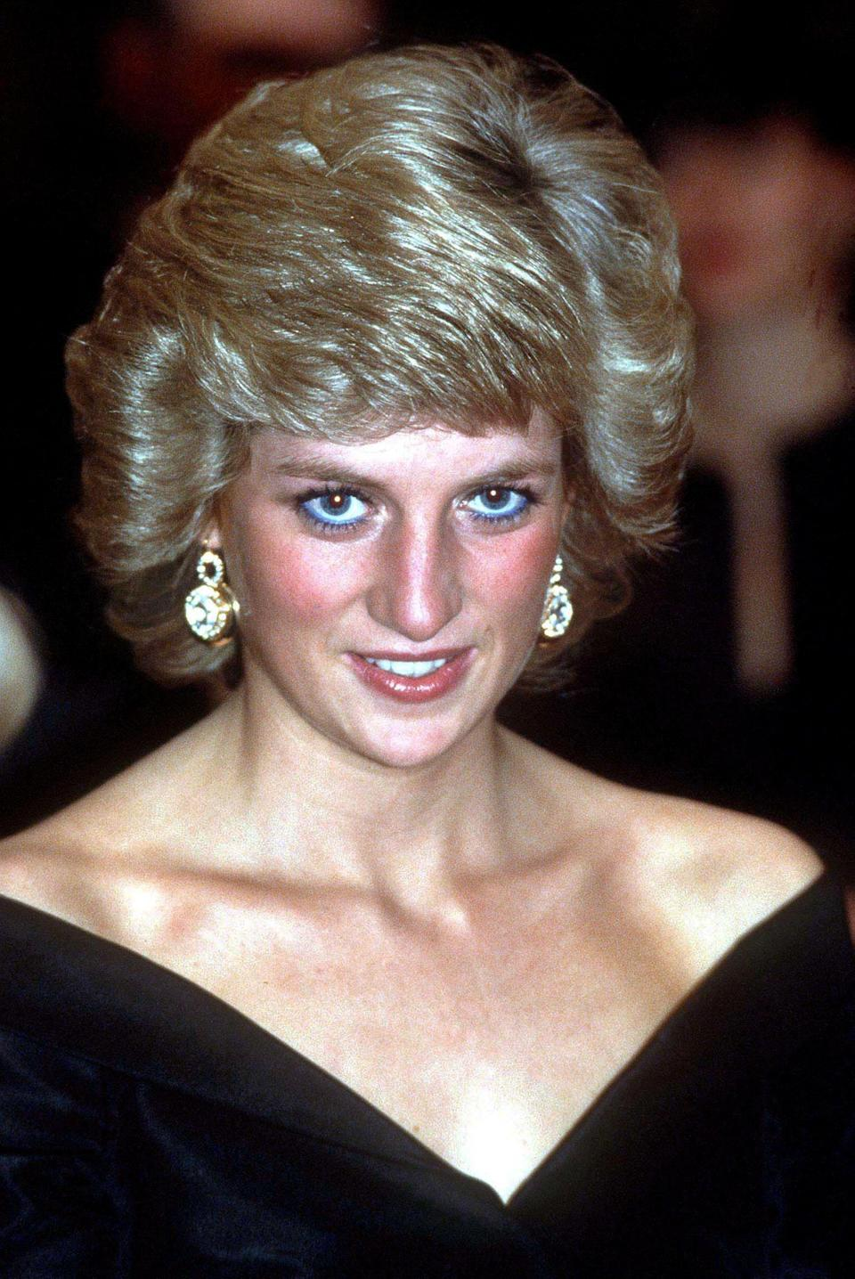 <p>During a visit to Germany in 1987, Princess Diana opted for a cold-shoulder black dress and sparkly earrings. She finished the look with a side-parted blow dry.<br><em>[Photo: PA]</em> </p>