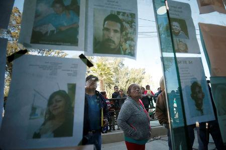 Residents look at pictures of people missing after an explosion of a fuel pipeline ruptured by oil thieves, in the municipality of Tlahuelilpan, state of Hidalgo, Mexico January 21, 2019. REUTERS/Mohammed Salem