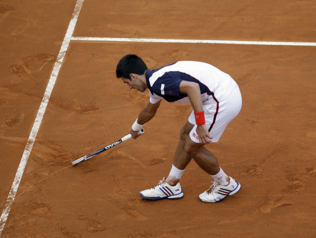 Serbia's Novak Djokovic carves a heart on the clay with his racket to celebrate his title at the Italian open tennis tournament in Rome, Sunday, May 18, 2014. Novak Djokovic extended his recent dominance over Rafael Nadal by rallying for a 4-6, 6-3, 6-3 victory Sunday to win the Italian Open for the third time. (AP Photo/Gregorio Borgia)