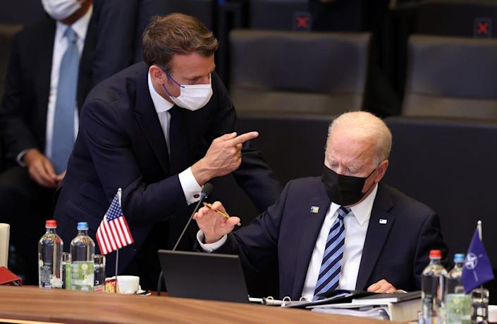 US President Joe Biden (R) and French President Emmanuel Macron (L) have a conversation ahead of the NATO summit at the North Atlantic Treaty Organization (NATO) headquarters in Brussels, on June 14, 2021.
