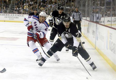 May 9, 2014; Pittsburgh, PA, USA; Pittsburgh Penguins center Evgeni Malkin (71) handles the puck as New York Rangers left wing Carl Hagelin (62) chases during the second period in game five of the second round of the 2014 Stanley Cup Playoffs at the CONSOL Energy Center. The Rangers won 5-1. Mandatory Credit: Charles LeClaire-USA TODAY Sports