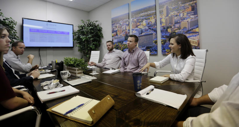 Bethany Babcock, co-owner of Foresite Commercial Real Estate, right, takes part in a staff meeting at her office in San Antonio, Tuesday, July 23, 2019.  For many small business owners, being a boss means helping staffers when they struggle Babcock, who runs a family friendly business, has bought a plane ticket for a staffer who needed to visit a relative on life support and paid moving expenses for a staffer who was having family problems, as well as permitting staff to bring their children to work.(AP Photo/Eric Gay)