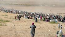 Syrian Kurds wait behind the border fence to cross into Turkey near the southeastern town of Suruc in Sanliurfa province, September 19, 2014. S REUTERS/Stringer
