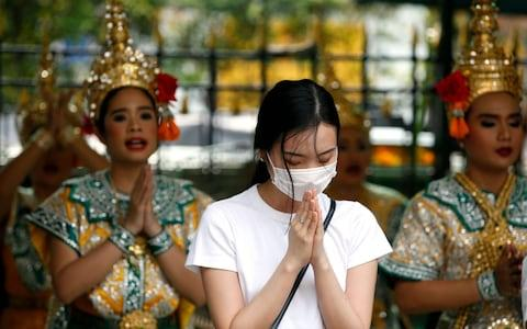 A worshipper wearing protective mask offers prayers in Bangkok after Thai health official confirmed its found two cases of coronavirus - Credit: RUNGROJ YONGRIT/EPA-EFE/REX