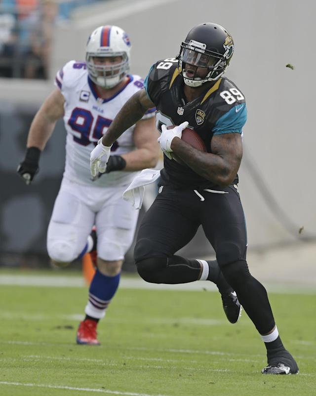 Jacksonville Jaguars tight end Marcedes Lewis (89) runs past Buffalo Bills defensive tackle Kyle Williams (95) after a reception during the first half of an NFL football game in Jacksonville, Fla., Sunday, Dec. 15, 2013. (AP Photo/John Raoux)