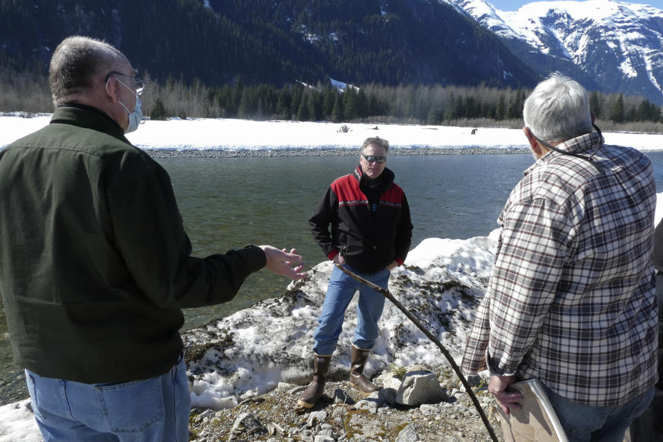 Alaska Gov. Mike Dunleavy, center, listens as residents discuss a levee they have concerns with on Thursday, April 22, 2021, in Hyder, Alaska. Hyder was among the southeast Alaska communities that Dunleavy visited as part of a one-day trip. (AP Photo/Becky Bohrer)