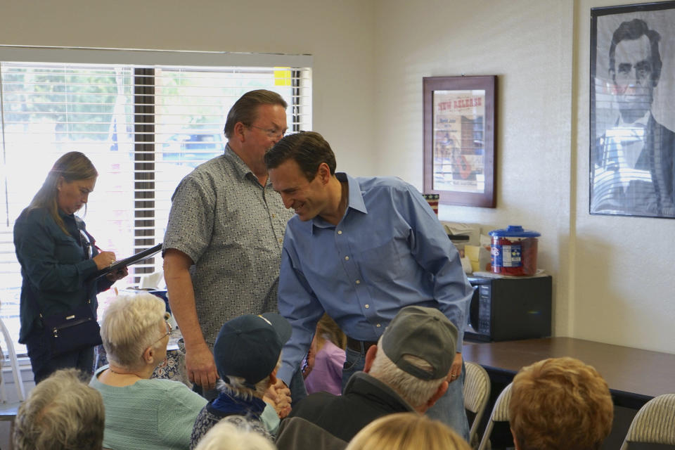 In this Sunday, Oct. 10, 2021, photo Republican Adam Laxalt greets supporters at the Douglas County Republican Party Headquarters on the final day of his Senate campaign's statewide tour in Gardnerville, Nev. Republican Laxalt hopes to win the race for Nevada's U.S. Senate seat by drawing stark between his positions and the direction he says Democrats and their allies in Big Tech, Hollywood and the media are taking the country. (AP Photo/Sam Metz)