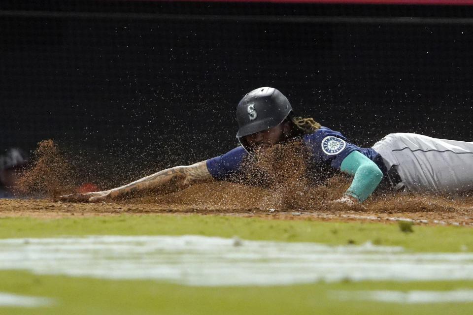 Seattle Mariners' J.P. Crawford scores on a sacrifice fly hit by Mitch Haniger during the seventh inning of a baseball game against the Los Angeles Angels Friday, Sept. 24, 2021, in Anaheim, Calif. (AP Photo/Mark J. Terrill)