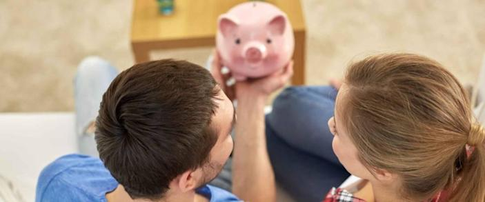 money, home, finance and relationships concept - close up of couple with piggy bank sitting on sofa