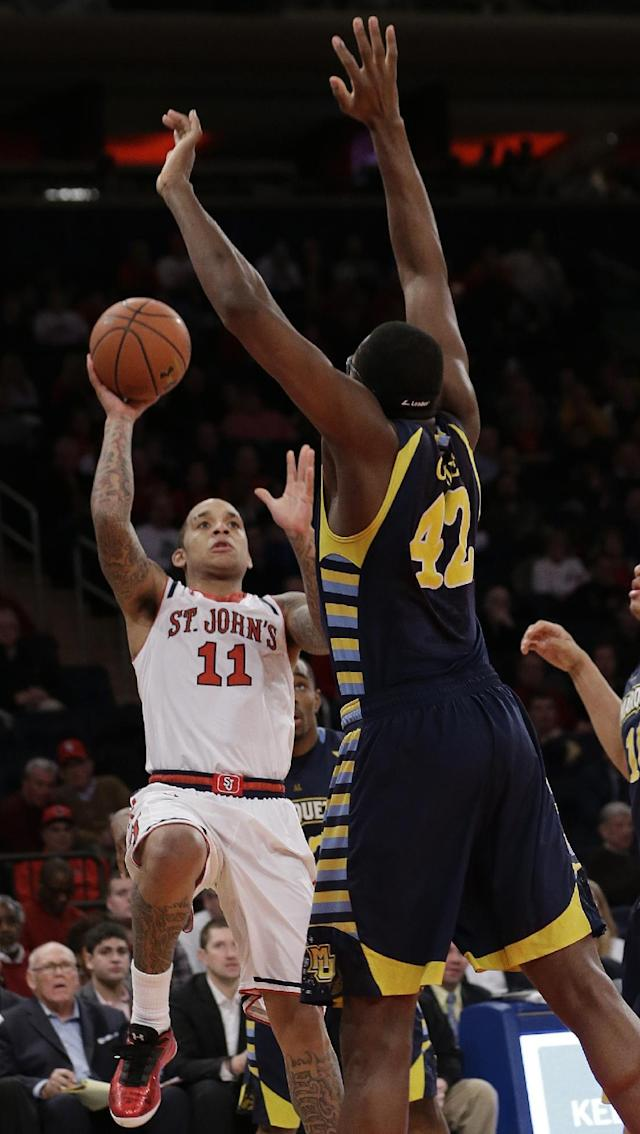 St. John's' D'Angelo Harrison (11) shoots over Marquette's Chris Otule (42) during the second half of an NCAA collage basketball game Saturday, Feb. 1, 2014, in New York. (AP Photo/Frank Franklin II)