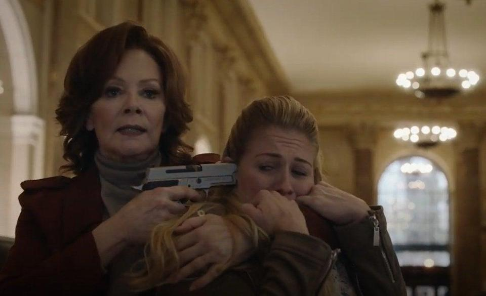A woman (Jean Smart) holding someone hostage with a gun pointed at the temple of the hostage