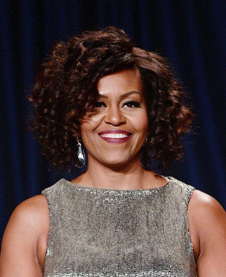 The first lady went ultra glam with tight curls, defined brows, matte berry lips, and a sparky silver dress.