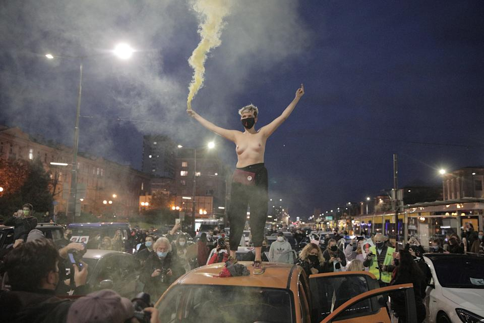 SENSITIVE MATERIAL. THIS IMAGE MAY OFFEND OR DISTURB A demonstrator holds a flare as she stands on top of a car during a protest against the ruling by Poland's Constitutional Tribunal that imposes a near-total ban on abortion, in Warsaw, Poland October 26, 2020. Jedrzej Nowicki/Agencja Gazeta via REUTERS ATTENTION EDITORS - THIS IMAGE WAS PROVIDED BY A THIRD PARTY. POLAND OUT. NO COMMERCIAL OR EDITORIAL SALES IN POLAND.