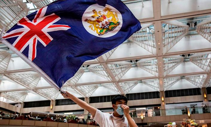 A pro-democracy protester waves a British colonial flag during a rally on 1 June.