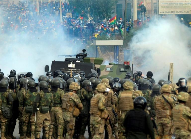 Bolivian riot police and soldiers clash with supporters of Bolivia's ex-President Evo Morales during a protest against the interim government in Sacaba, Chapare province, Cochabamba department on November 15, 2019