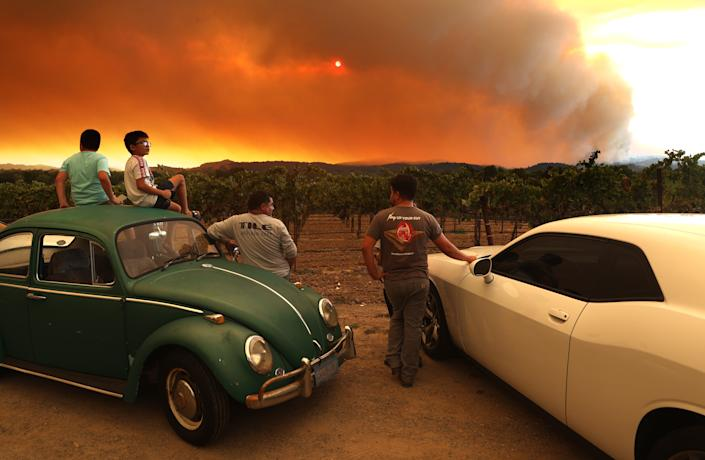 Residents sit next to a vineyard as they watch the LNU Lightning Complex Fire burn in nearby hills on Aug. 20 in Healdsburg, Calif.