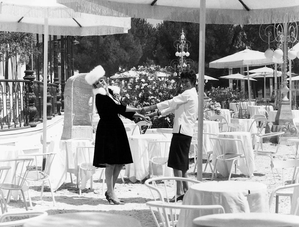 Black and white: Two women in stylish outfits standing with arms stretched toward one another, holding hands at a beautiful outdoor dining area with tables, chairs, and fringed umbrellas, still from 8 1/2