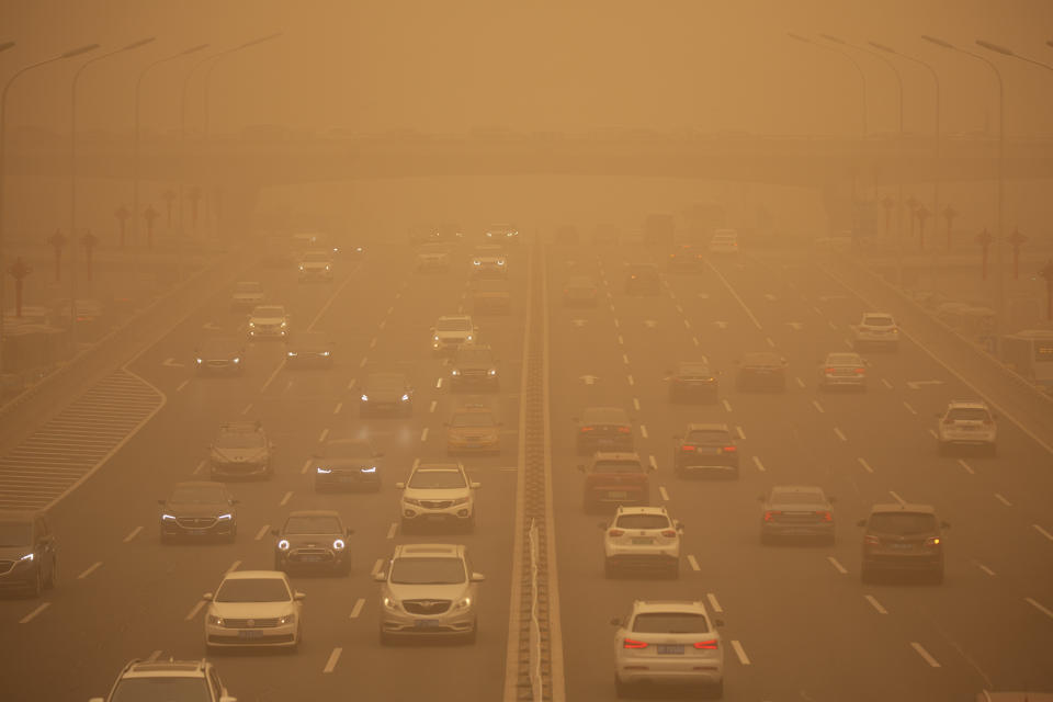Cars are driven along an expressway amid a sandstorm during the morning rush hour in Beijing. (AP Photo/Mark Schiefelbein)