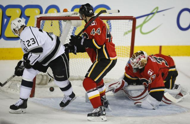 Los Angeles Kings' Dustin Brown, left, scores on Calgary Flames goalie Joni Ortio, right, from Finland, as Flames' Chris Butler watches during the first period of an NHL hockey game Thursday, Feb. 27, 2014, in Calgary, Alberta. (AP Photo/The Canadian Press, Jeff McIntosh)