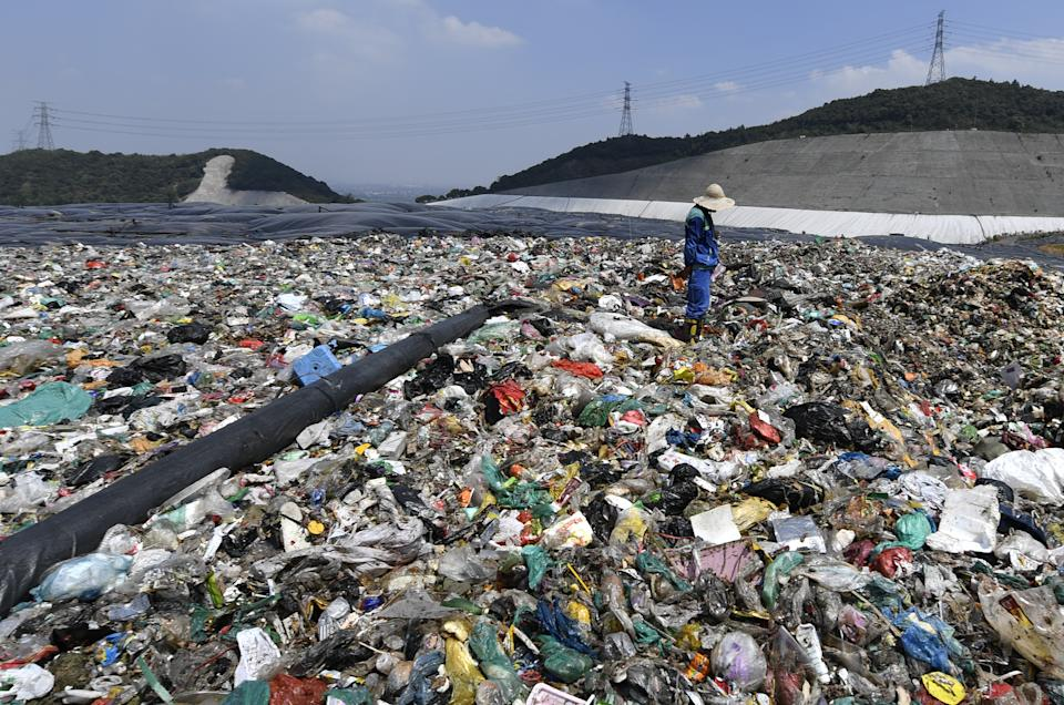 HANGZHOU, CHINA - AUGUST 07: A worker prepares to cover the waste with a capping layer at the Tianziling landfill site on August 7, 2019 in Hangzhou, Zhejiang Province of China. (Photo by Wang Chuan/Visual China Group via Getty Images)