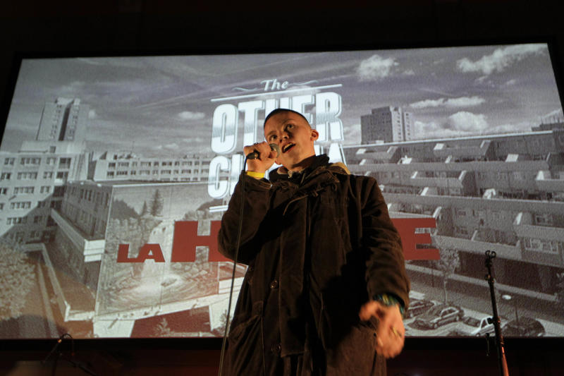 "This Wednesday, May 2, 2012 photo poet, Sonny Green recites a poem before a free screening of ""La Haine"" (""Hate""), a powerful 1995 film about alienated youth on the impoverished high-rise fringes of Paris at Broadwater Farm Community Center in north London. Isaac Densu lives in Broadwater Farm, a large, concrete public housing estate in Tottenham, the gritty and deprived district where last year's riots began. Unemployment is high, and young people face many temptations to get into trouble. Densu thinks he knows what might help: a good movie. The film-loving 26-year-old thinks watching movies can help his neighbors expand their horizons and embrace creativity, rather than violence. (AP Photo/Sang Tan)"