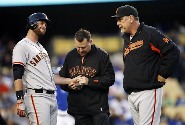 San Francisco Giants' Brandon Belt, left, reacts after being hit by a pitch on his left hand as a trainer and manager Bruce Bochy, right, attend to him against the Los Angeles Dodgers during the second inning of a baseball game, Friday, May 9, 2014, in Los Angeles. (AP Photo/Danny Moloshok)