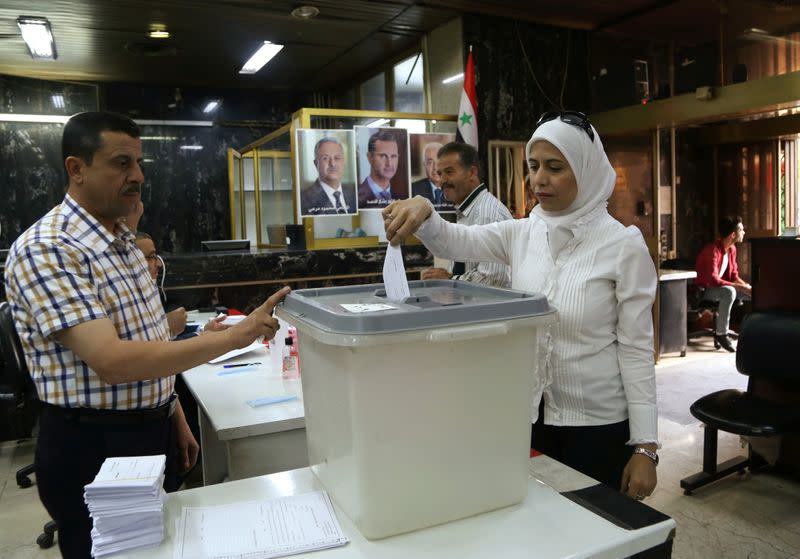A woman casts her vote at a polling station during the presidential elections in Damascus