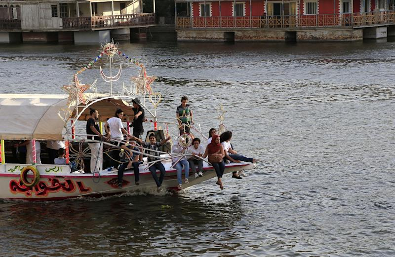 Egyptians enjoy a boat ride along the Nile River, in Cairo, Egypt, Tuesday, May 28, 2013. (AP Photo/Hassan Ammar)