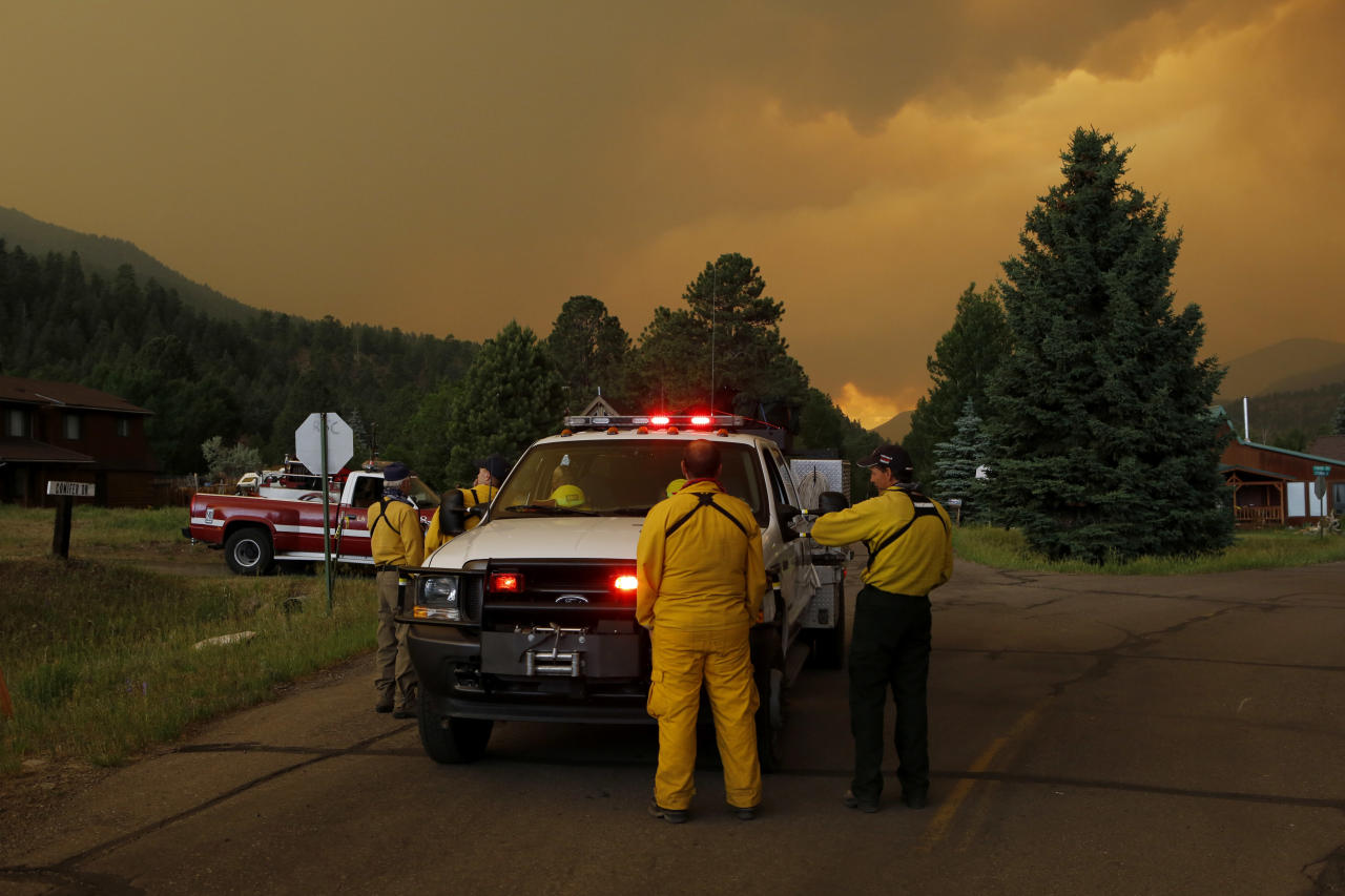 Firefighters stage in a residential area in South Fork, Colo., as they monitor a wildfire that burns west of town on Friday evening June 21, 2013. The town was evacuated and U.S. 160 that passes through it was closed. (AP Photo/Ed Andrieski)