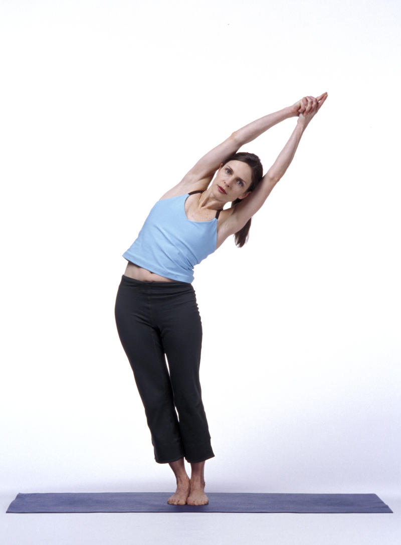 Woman Bending Sideways in Yoga Pose With Arms Raised