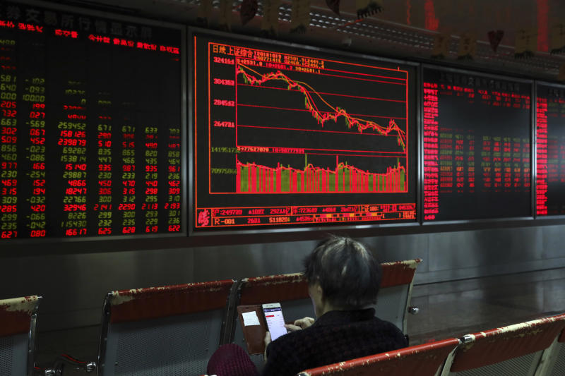 A Chinese woman monitors stock prices at a brokerage in Beijing, Friday, Oct. 19, 2018. Asian stock markets sank Friday after Wall Street declined on losses for tech and industrial stocks and Chinese economic growth slowed. (AP Photo/Ng Han Guan)
