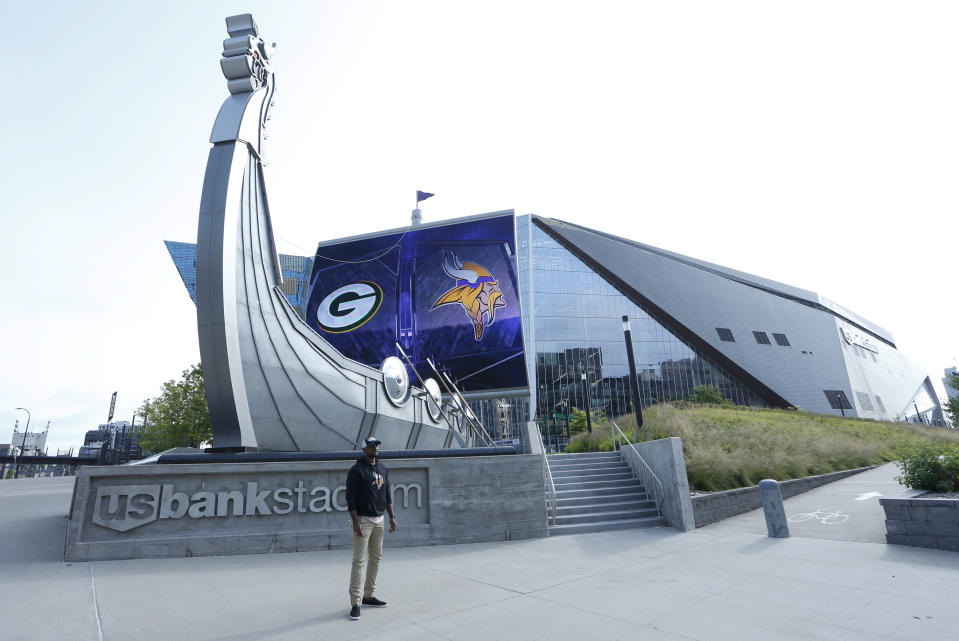 A lone fan has his picture taken in front of U.S. Bank Stadium before an NFL football game between the Minnesota Vikings and the Green Bay Packers, Sunday, Sept. 13, 2020, in Minneapolis. (AP Photo/Bruce Kluckhohn)