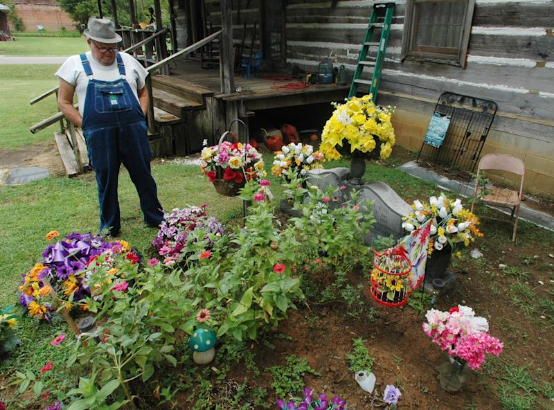 In this Friday, Aug. 10, 2012 photo, James Davis, 73, stands over the grave of his wife, Patsy, in the front yard of the home they shared in Stevenson, Ala. The city sued to make Davis move his wife's remains from the residential tract, and Davis is asking the Alabama Court of Civil Appeals to block an order requiring him to disinter her remains. (AP Photo/Jay Reeves)