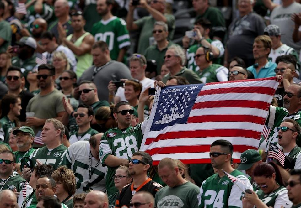 Fans hold an America Flag in remembrance of the 9/11 attacks during the game between the Cincinnati Bengals and the New York Jets at MetLife Stadium on September 11, 2016 in East Rutherford, New Jersey (AFP Photo/Streeter Lecka)