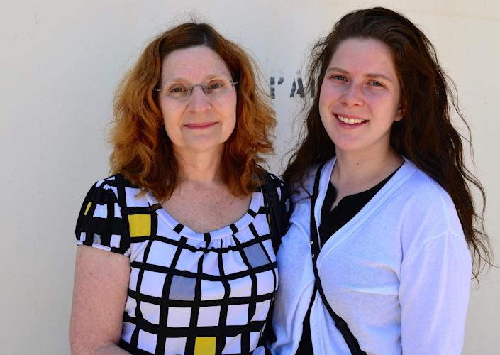 Gloria Snekszer, left, and her daughter, Amanda, who came to Guantanamo to observe legal pretrial proceedings in the case of five men charged in the Sept. 11, 2001, terrorist attack, pose for a photo at the U.S. naval base in Guantanamo, Cuba, April 17, 2014. Gloria Snekszer's sister, Vicki Linn Yancey, was aboard American Airlines Flight 77, which crashed into the Pentagon. (AP Photo/Stijn Hustinx)
