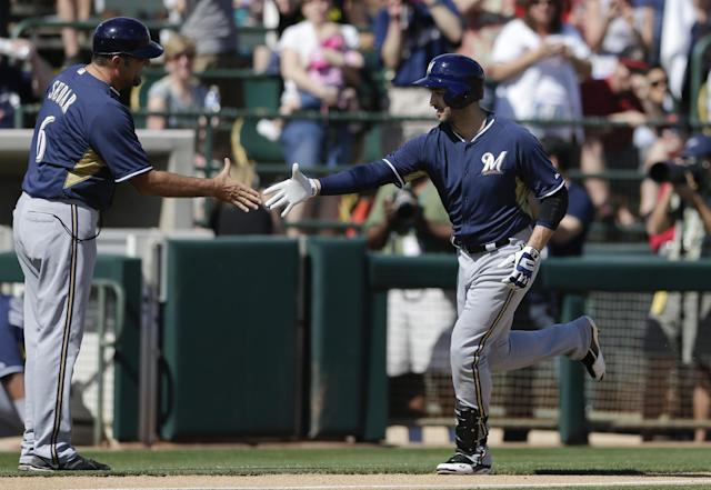 Milwaukee Brewers' Ryan Braun, right, is greeted by third base coach Ed Sedar after hitting a home run during the first inning of a spring training baseball game against the Oakland Athletics, Thursday, Feb. 27, 2014, in Scottsdale, Ariz