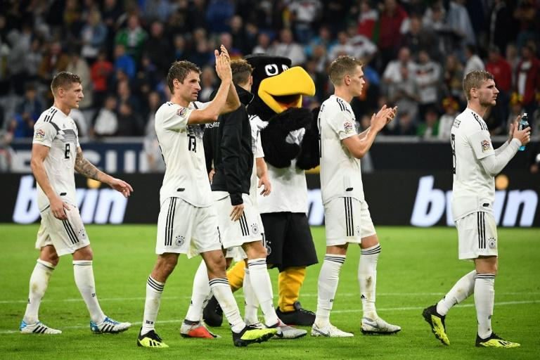 Toni Kroos (L) and Thomas Mueller (2ndL) take the applause from the German fans after Thursday's draw with France
