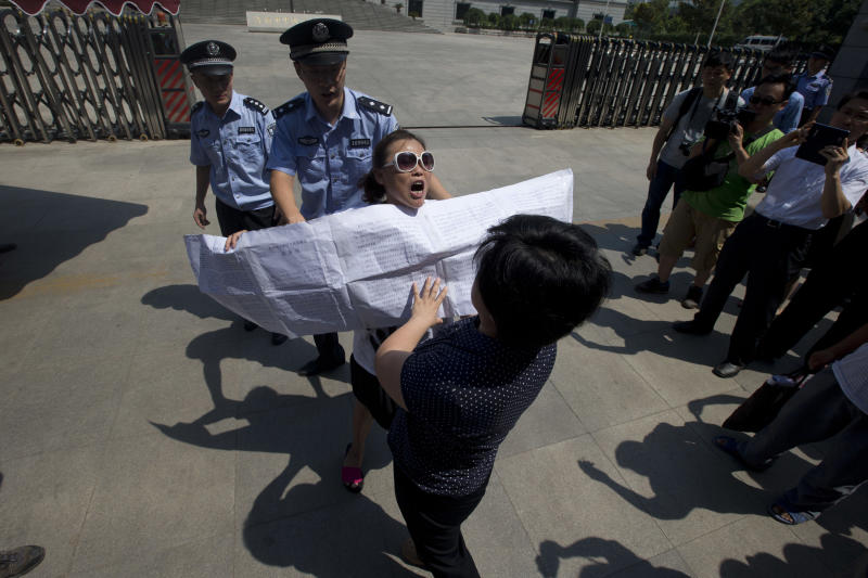 A Chinese woman, center with sunglasses, protests outside the Jinan Intermediate People's Court in Jinan, eastern China's Shandong province Wednesday, Aug. 21, 2013. Former Chinese politician Bo Xilai will stand trial at the court on Thursday on charges of corruption and abuse of power. Individual protestors have turned up at the court hoping to take advantage of media attention around Bo's trial to air their own grievances about China's legal system. (AP Photo/Ng Han Guan)
