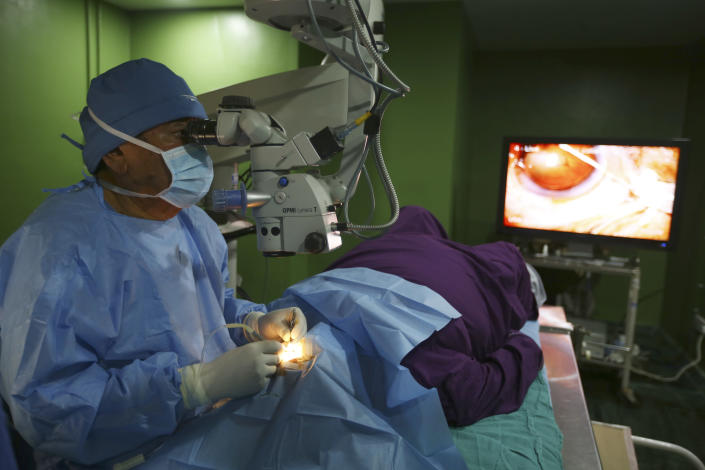 """Dr. Sanduk Ruit performs cataract surgery at the Tilganga Eye Center in Kathmandu, Nepal, March 26, 2021. Nepal's """"God of Sight"""" eye doctor renowned for his innovative and inexpensive cataract surgery for the poor is taking his work beyond the Himalayan mountains to other parts of the world so there is no more unnecessary blindness in the world. Ruit, who has won many awards for his work and performed some 130,000 cataract surgery in the past three decades, is aiming to expand his work beyond the borders of his home country and the region to go globally. (AP Photo/Niranjan Shrestha)"""
