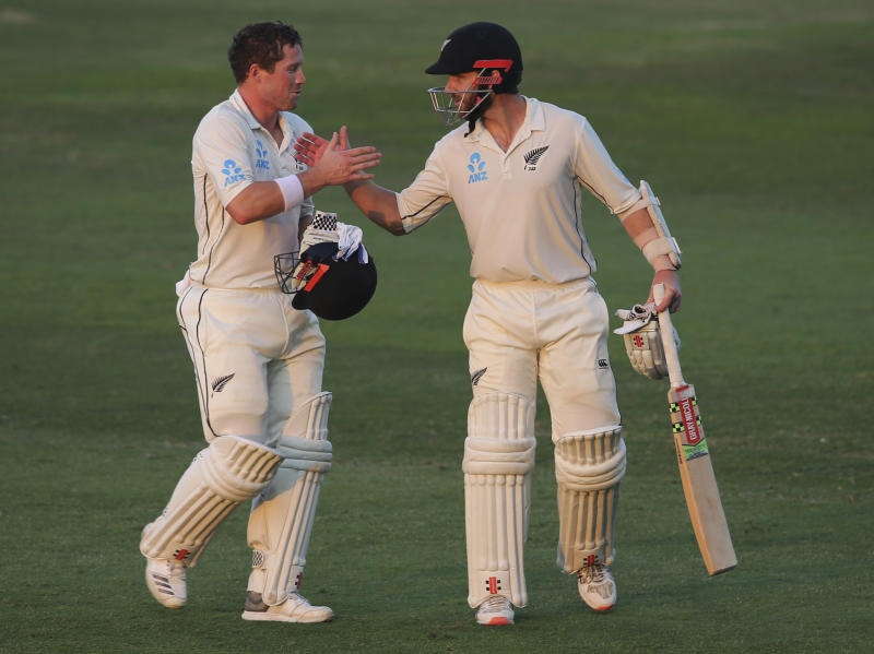 New Zealand's batsmen, Henry Nicholls, left, and Kane Williamson shakes hands as they leave the pitch at the end of forth day in their test match against Pakistan in Abu Dhabi, United Arab Emirates, Thursday, Dec. 6, 2018. (AP Photo/Kamran Jebreili)