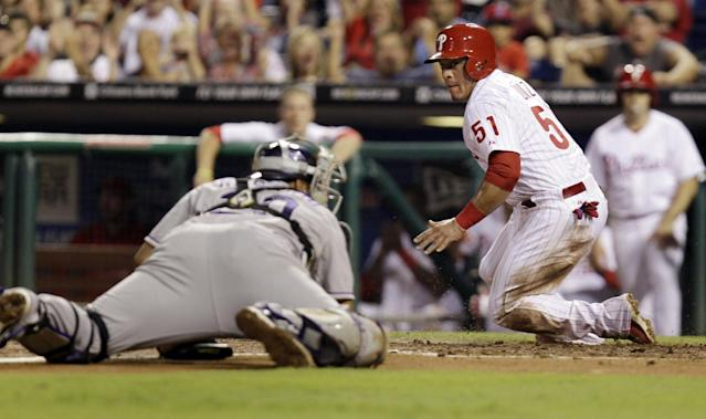 Philadelphia Phillies' Carlos Ruiz is safe at home on a sacrifice fly ball to center field by Domonic Brown before Colorado Rockies catcher Willin Rosario can make the tag in the third inning in a baseball game, Tuesday, Aug. 20, 2013, in Philadelphia. (AP Photo/Laurence Kesterson)