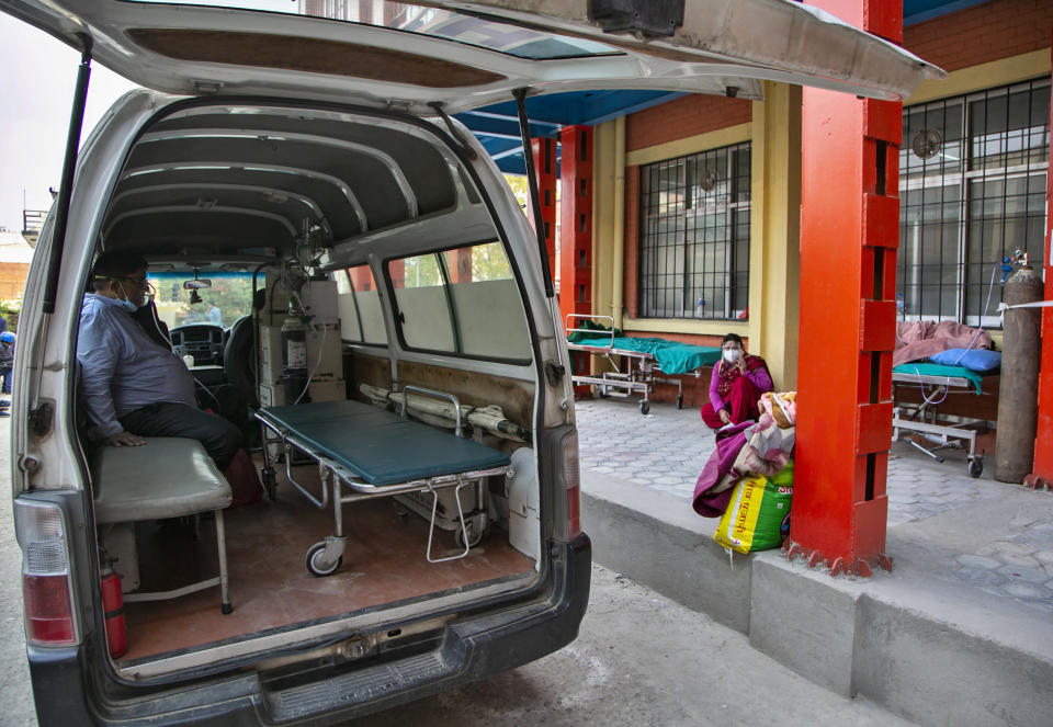 A COVID-19 patient receives oxygen in an ambulance outside an emergency ward as he waits for a bed to be allotted at a hospital in Kathmandu, Nepal, Thursday, May 6, 2021. Nepal's main cities and towns including the capital Kathmandu has been in lockdown since last month as the number coronavirus cases and deaths continue to rise. (AP Photo/Niranjan Shrestha)