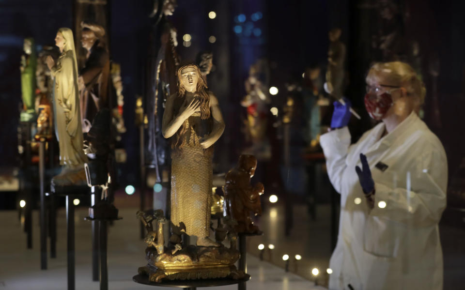 Kate Perks, Senior Collections Care Conservator prepares a display of Deities and Saints, displayed at the Science Museum in London, Monday, May 17, 2021. The Science Museurm reopens to the public on Wednesday. (AP Photo/Kirsty Wigglesworth)