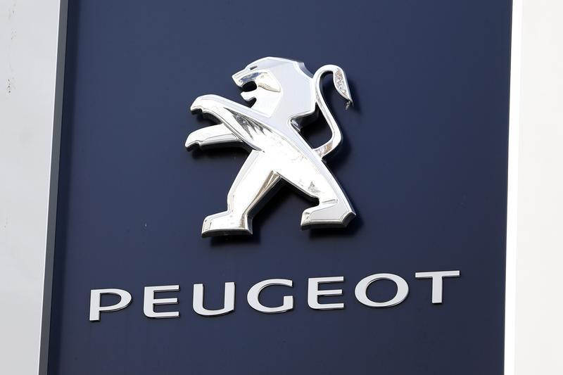 A Peugeot company logo is seen outside an automobile dealership in Paris