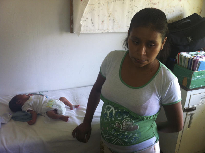 """In this Oct. 6, 2013 photo, 29-year-old Irma Lopez stands next to her newborn son Salvador at a clinic in the town of Jalapa de Diaz, Mexico. Mexico officials have suspended a health center director after Lopez, an indigenous woman, was denied entry to his clinic and was forced to give birth on the lawn. A nurse kicked Lopez out of the clinic Oct. 2, claiming she was """"still not ready"""" and had to wait for a doctor. After an hour and half, Lopez gave birth while grabbing the wall of a house next to the clinic. (AP Photo/Chema Alvarez)"""